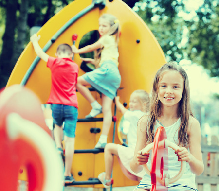 Cheerful  girl with long hair in school age sitting on swing on children's playground outdoors