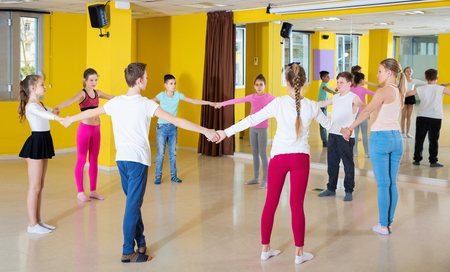 Positive  teenage boys and girls practicing circle dance with female trainer in dance hall