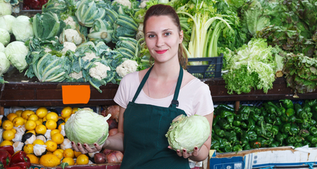 Seller is holding green cabbage on her workplace in the market.