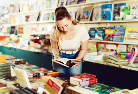Portrait of smiling young woman buying textbooks in book store