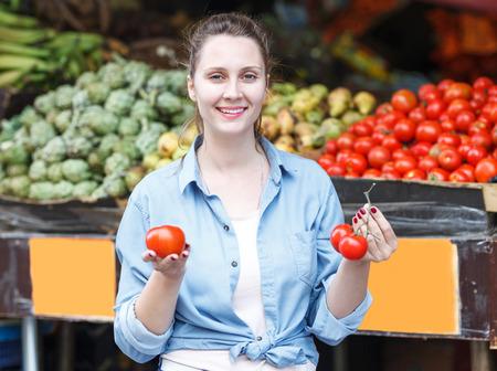 Woman is choosing fresh tomato in the market. Stok Fotoğraf