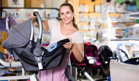 Young positive smiling pregnant woman carefully choosing infant car seat in kids mall