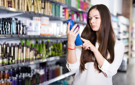 Serious young woman looking hair cair products at cosmetical  shop