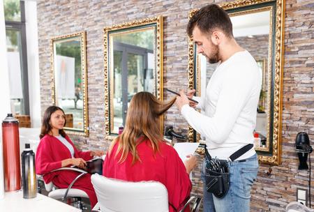 Cheerful positive glad man professional hairdresser cut female's hair in hairdressing salon Standard-Bild
