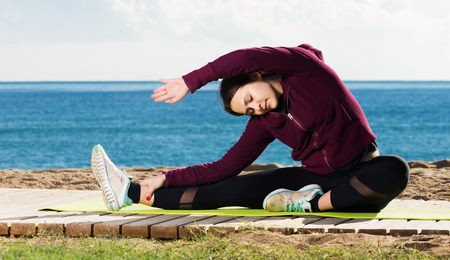 Portrait of smiling young woman doing yoga asanas and pranayama at seaside Stok Fotoğraf