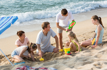 happy large family with four children playing together with sand toys and active games on beach  Stock Photo