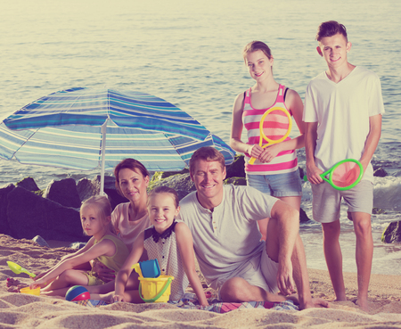 Portrait of cheerful big family - man and woman with four kids having beach umbrella and toys on sandy coast. Focus on standing girl Banco de Imagens