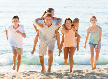 Active parents with four children in different ages sitting on parents back taking walk on beach