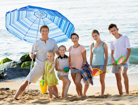 Large friendly smiling family of six people standing together on beach on summer day