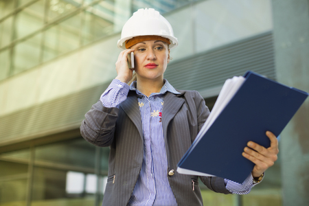 Adult woman architect in helmet with paper documents talking phone Stock Photo