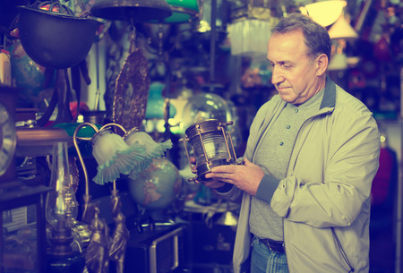 Middle aged man buying retro handicrafts on indoor flea market Stock Photo