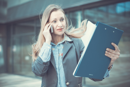 Portrait of employee woman working outdoors and talking phone
