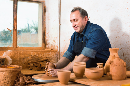 Elderly master among the pottery at the workshop Stock Photo