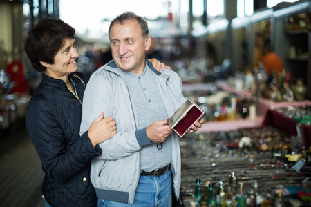 Happy man and his wife are visiting market of old things and choosing old casket outdoors. Stock Photo