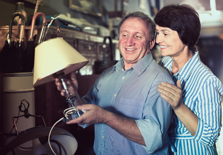 interested mature couple is shopping the old lamp for home in the antique store