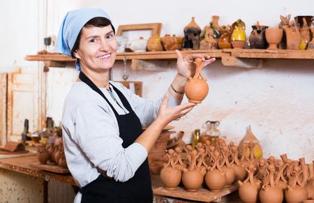 Smiling senior female  potter working at workshop