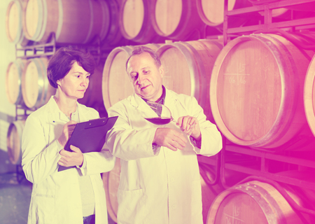 Expert and elderly male wine maker estimate quality of wine in cellar