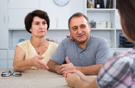 Senior parents attentively listening and talking to woman indoors
