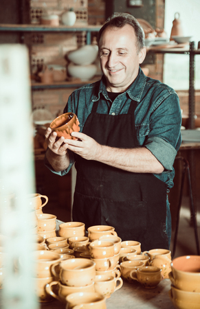 Positive mature master among the pottery at the workshop