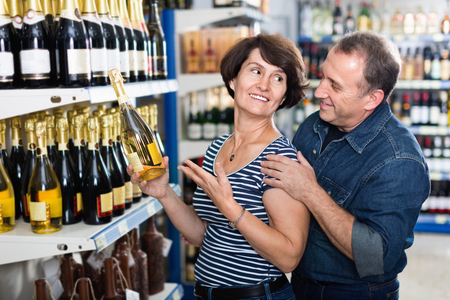 Portrait of an elderly couple buying a wine at the grocery store