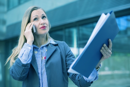 Portrait of employee woman working outdoors and talking phone  Banco de Imagens