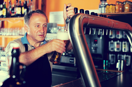 Barman is pouring beer with foam for client in the bar.