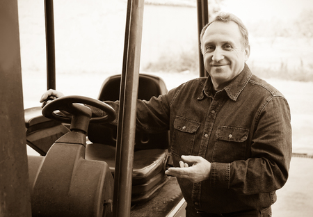 Mature worker of winery goes driving loader