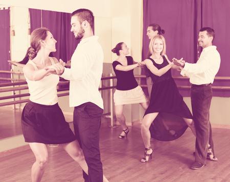 adult european men and women enjoying of tango in class