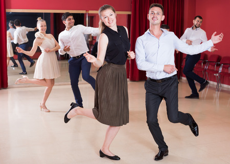 Young positive people dancing twist in pairs Stockfoto