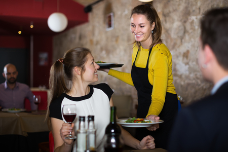 Positive waitress bringing delicious salads to visitors in cafe Stock Photo