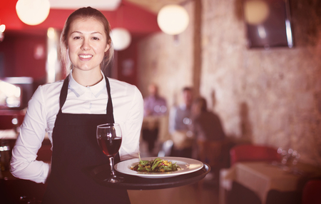 Portrait of smiling cheerful positive waitress with serving tray meeting restaurant guests Stock Photo