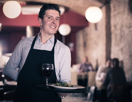 Positive waiter holding tray at restaurant with customers his behind