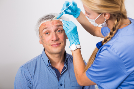 Female doctor is doing injection to patient in skin of face in estetic clinic.