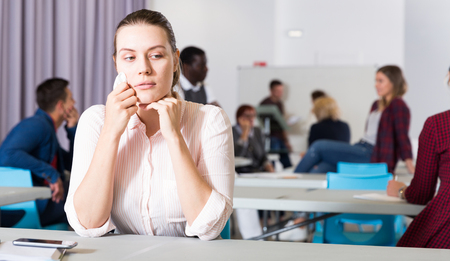 Portrait of unhappy girl sitting apart in class, having conflict with fellows students