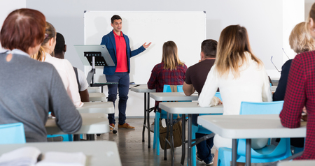 Smiling male teacher giving presentation for students in lecture hall  Stock Photo