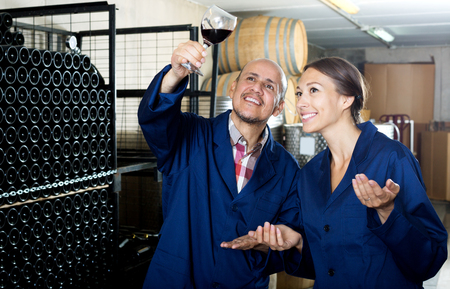Two happy winery workers holding glass of wine in aging section of factory 免版税图像 - 102703484