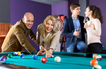 Cheerful group of friends playing billiards and smiling in billiard club
