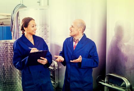 男性1が発酵セクションで働いている間にメモを取って喜ぶ女性のワイナリー労働者 写真素材 - 102697868