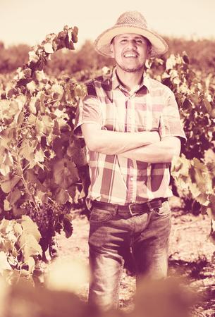 Cheerful man gardener standing in grapes tree yard