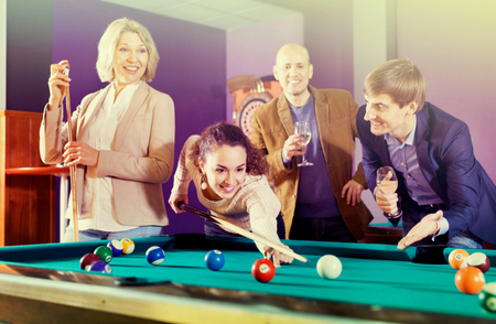 Group of cheerful pretty positive friends playing billiards and smiling in night club Stockfoto
