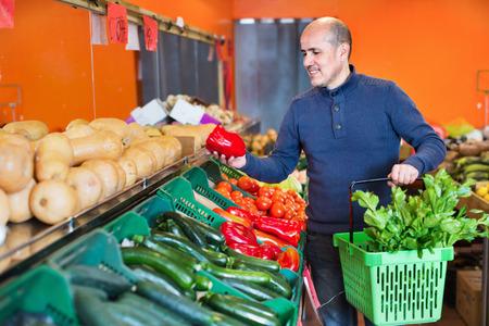 Portrait of mature smiling  positive man purchasing seasonal veggies in farm food store 免版税图像 - 102697879