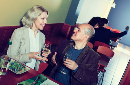 Ordinary smiling mature couple having dinner at restaurant table