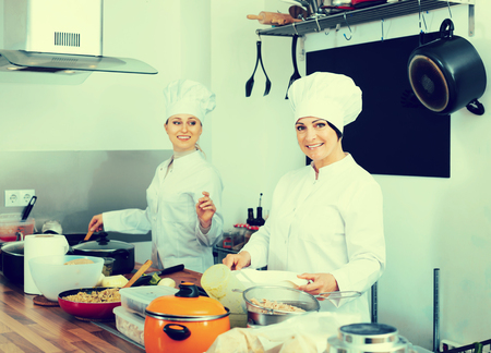 Women chefs cooking food at cafe's kitchen