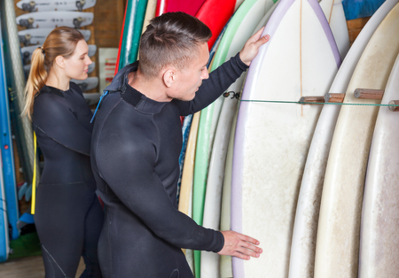 Young man and woman dressed surfing suits checking surfboards on racks in a surf club. Focus on man