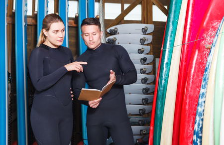 Two surf coaches making complete list of surfboards suitable for rent in surf club Stock fotó