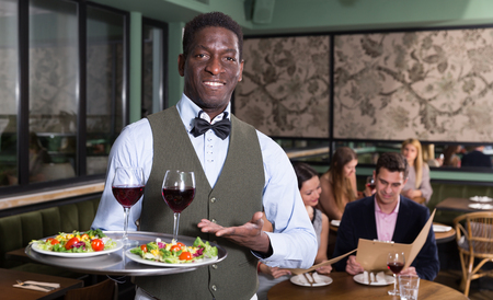 Hospitable African American waiter standing with serving tray, recommending dishes in restaurant