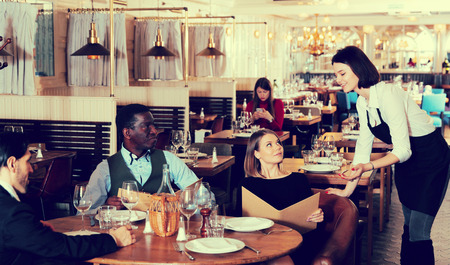 Hospitable waitress talking with restaurant guests, recommending dishes from menu card