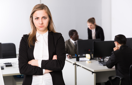 Tired businesswoman standing in office on backround  with working colleagues Stok Fotoğraf