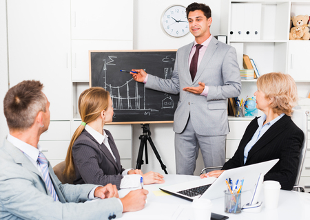 Successful businessman presenting new business strategy to partners in office