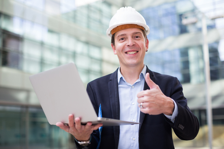 Cheerful male builder talking about work at the laptop at the street